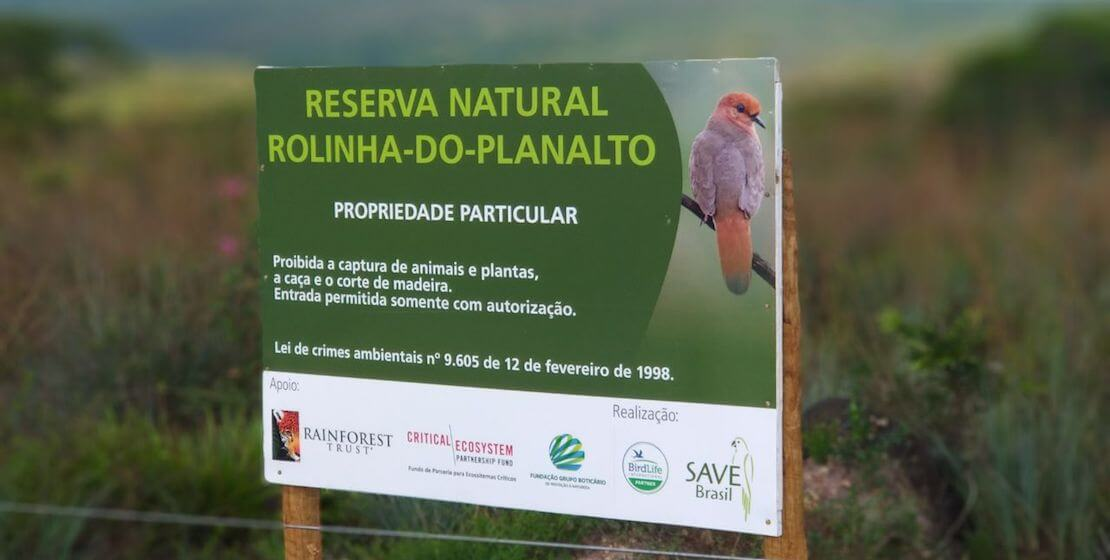 "Sign for ""Reserva Natural Rolinha-Do-Planalto with image of  blue-eyed ground-dove and list of funders, including CEPF, at the bottom."