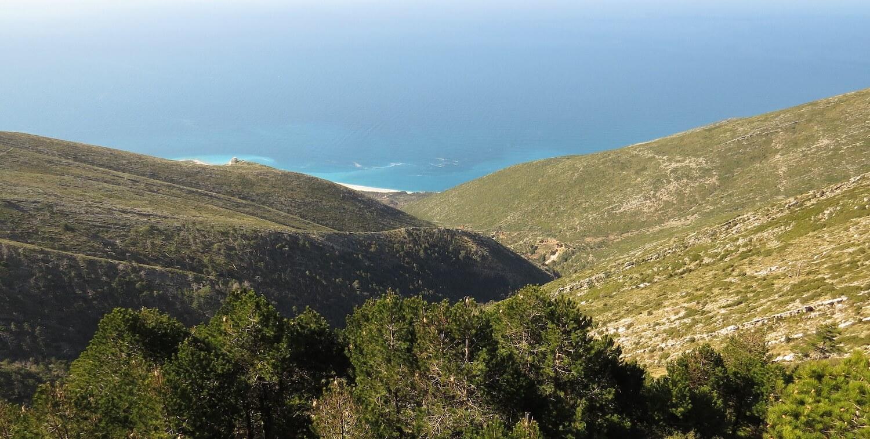 Landscape of rolling hills, blue water beyond.