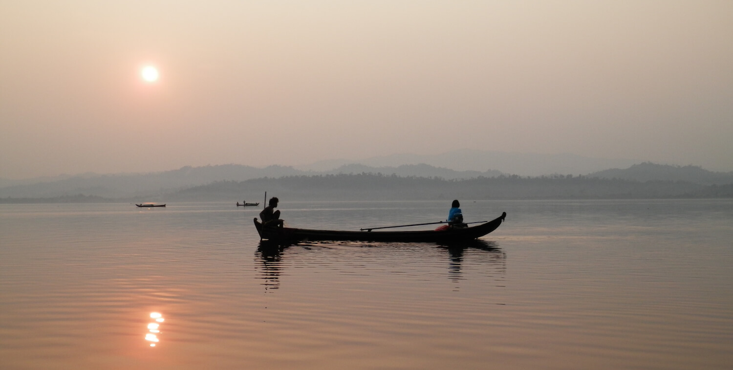Canoe with two people at sunrise or sunset.