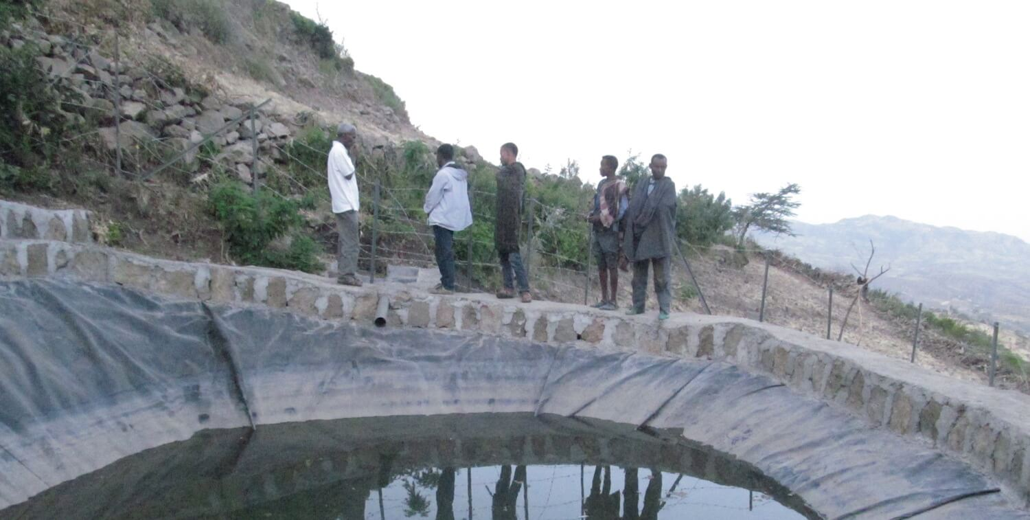 A few men standing by man-made pool of water.