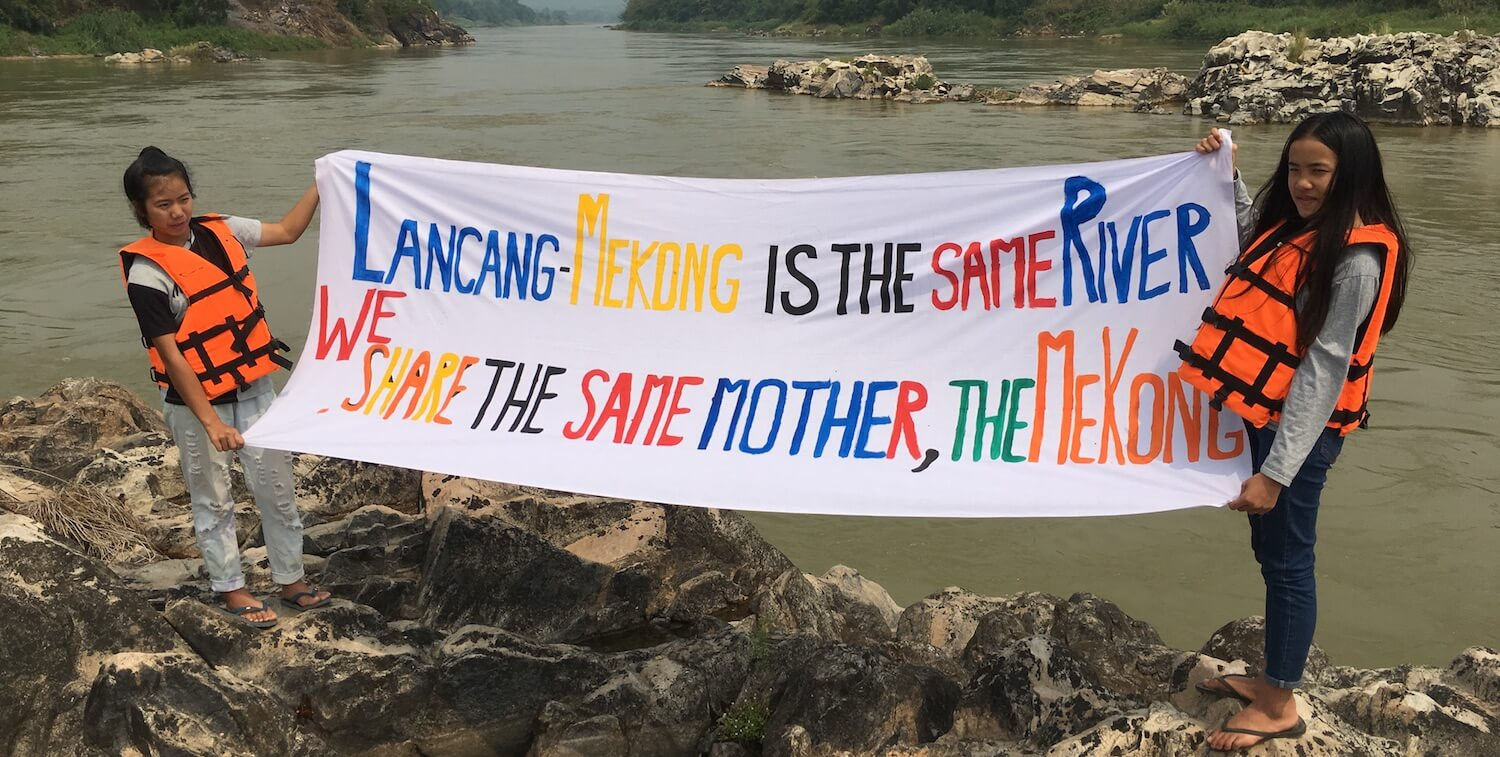 """Two girls standing in front of river holding hand-made sign that says """"Lancang-MEkong is the Same River We Share the Same Mother, the Mekong"""""""