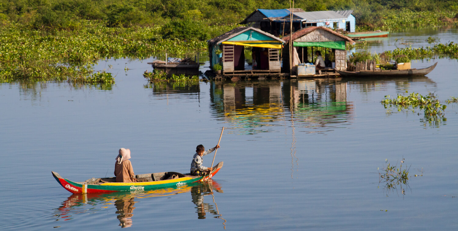 One adult and one child in brightly colored canoe, behind them, structures built on river.