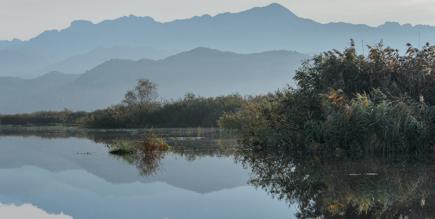 Mountains in background reflecting in lake water in foreground.