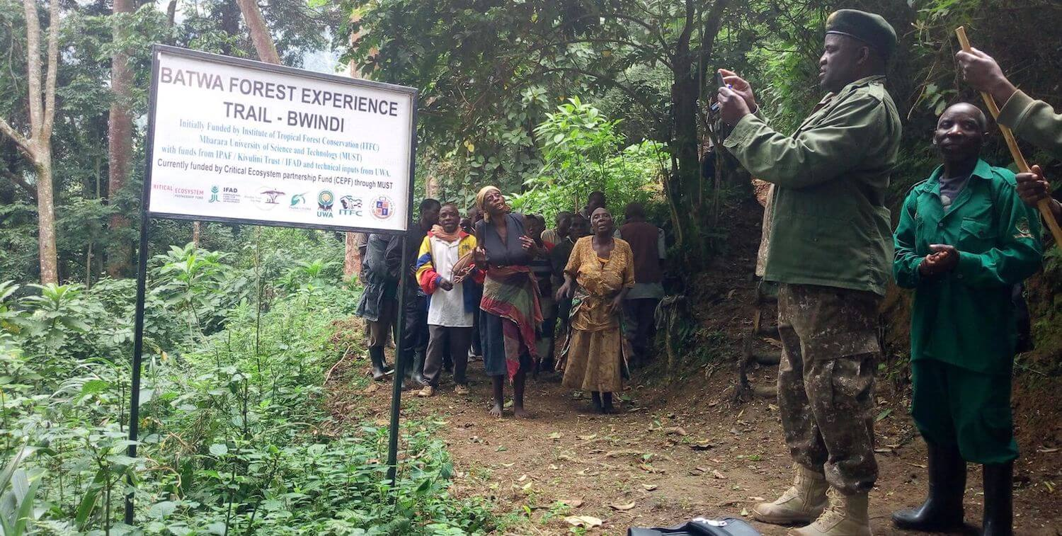 Batwa Forest Experience Trail - Bwindi sign with group dancing in backround.