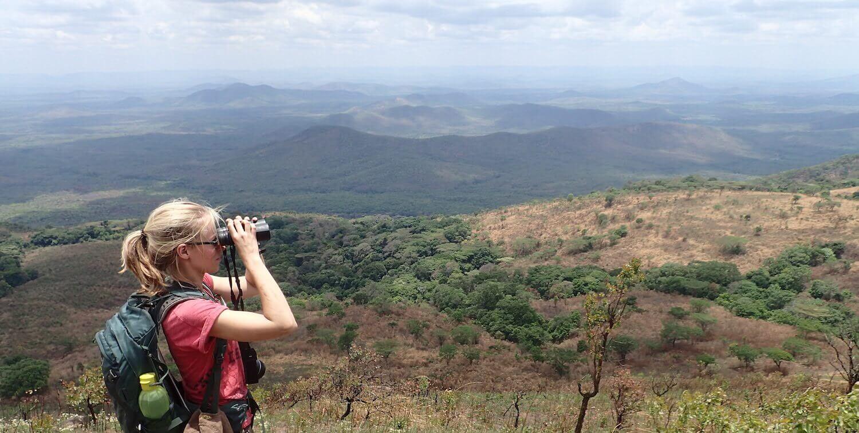 Woman looking through binoculars out at vista