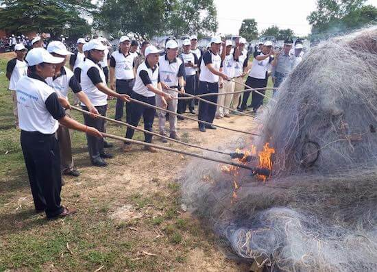 A group of people in matching white shirts and hats, take long sticks with ends on fire to large pile of nets.