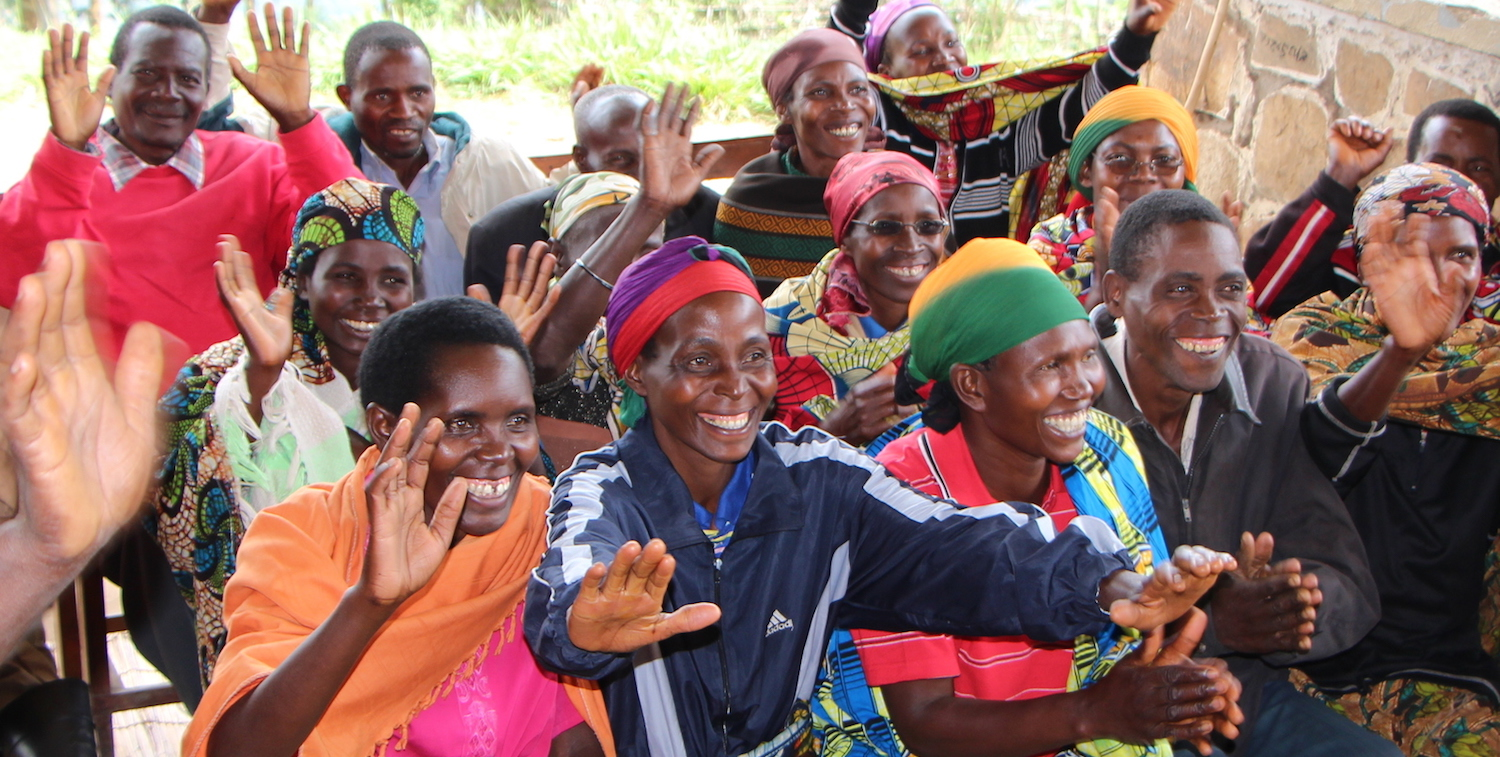 Group of women and men smiling and raising their hands.