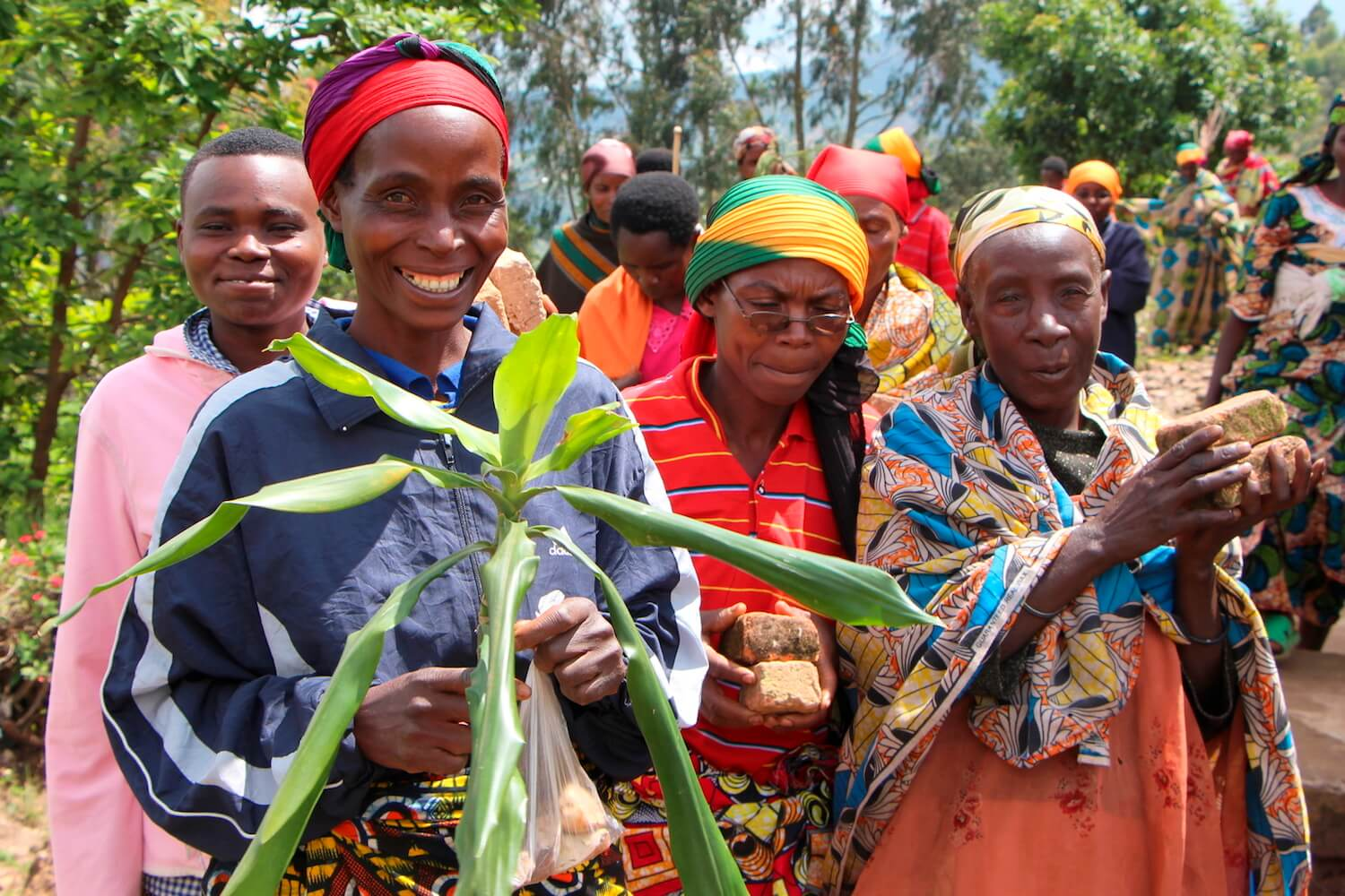 A few women, and one man, in brightly colored clothing. Woman in front is holding plant and smiling at camera.