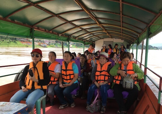 Group of women wearing orange life vests traveling on open air boat.