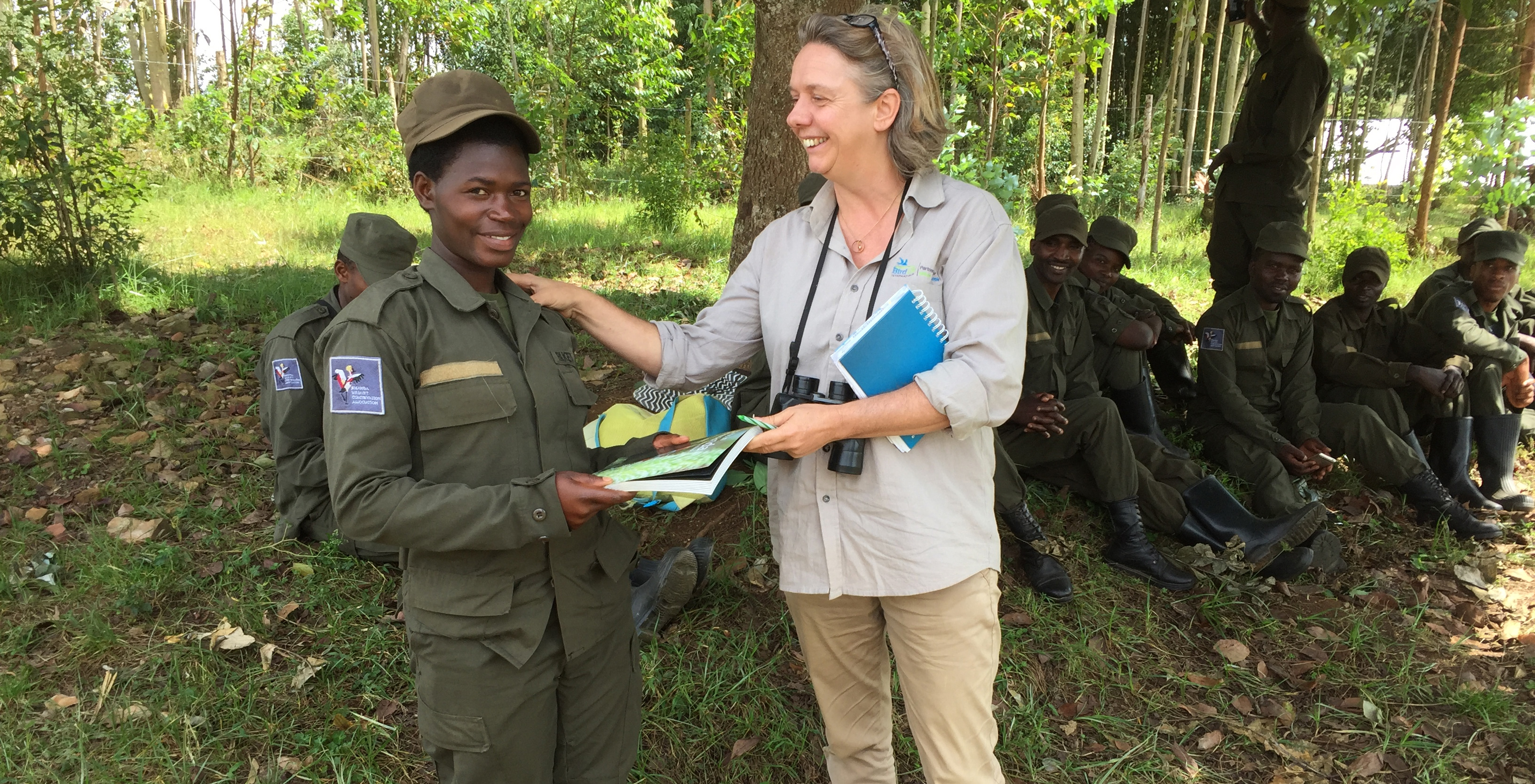 Regional Implementation Team leader stands smiling with marsh ranger and more marsh rangers sit behind them