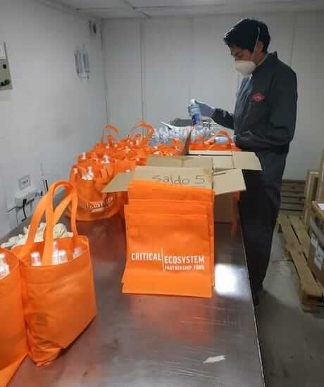 Man wearing mask prepares CEPF-branded bags of supplies.