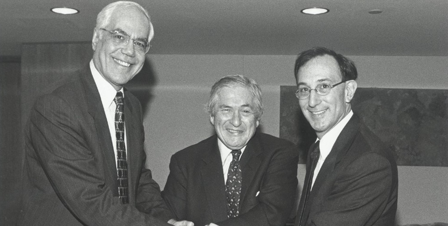 Three men in suits gather together, smiling.