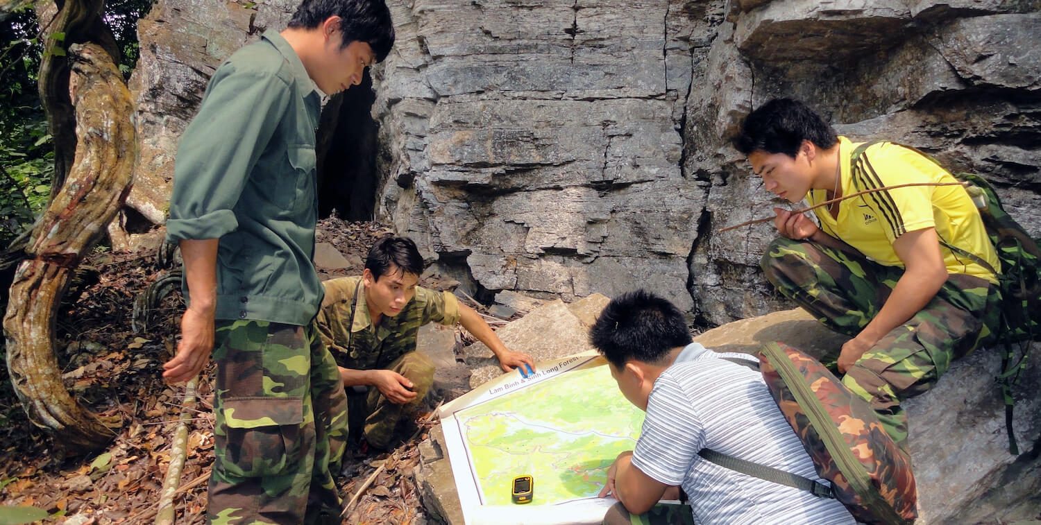 Four men, outside, bent over looking at large map laid out on a rock.