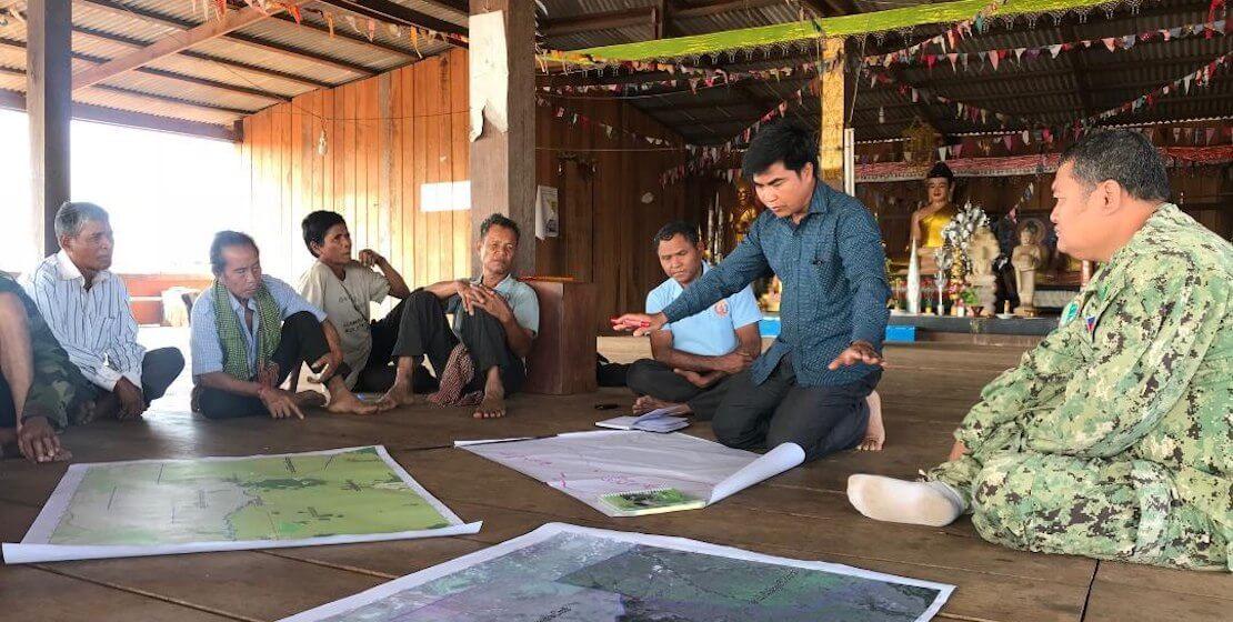 A handful of men sitting on floor around a few maps.
