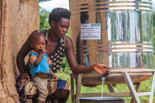 Woman with young child opens a metal drum's faucet, dispensing water.