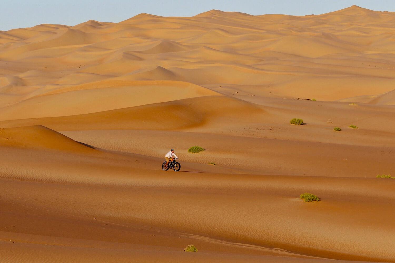 Cyclist appear small amid sand dunes.