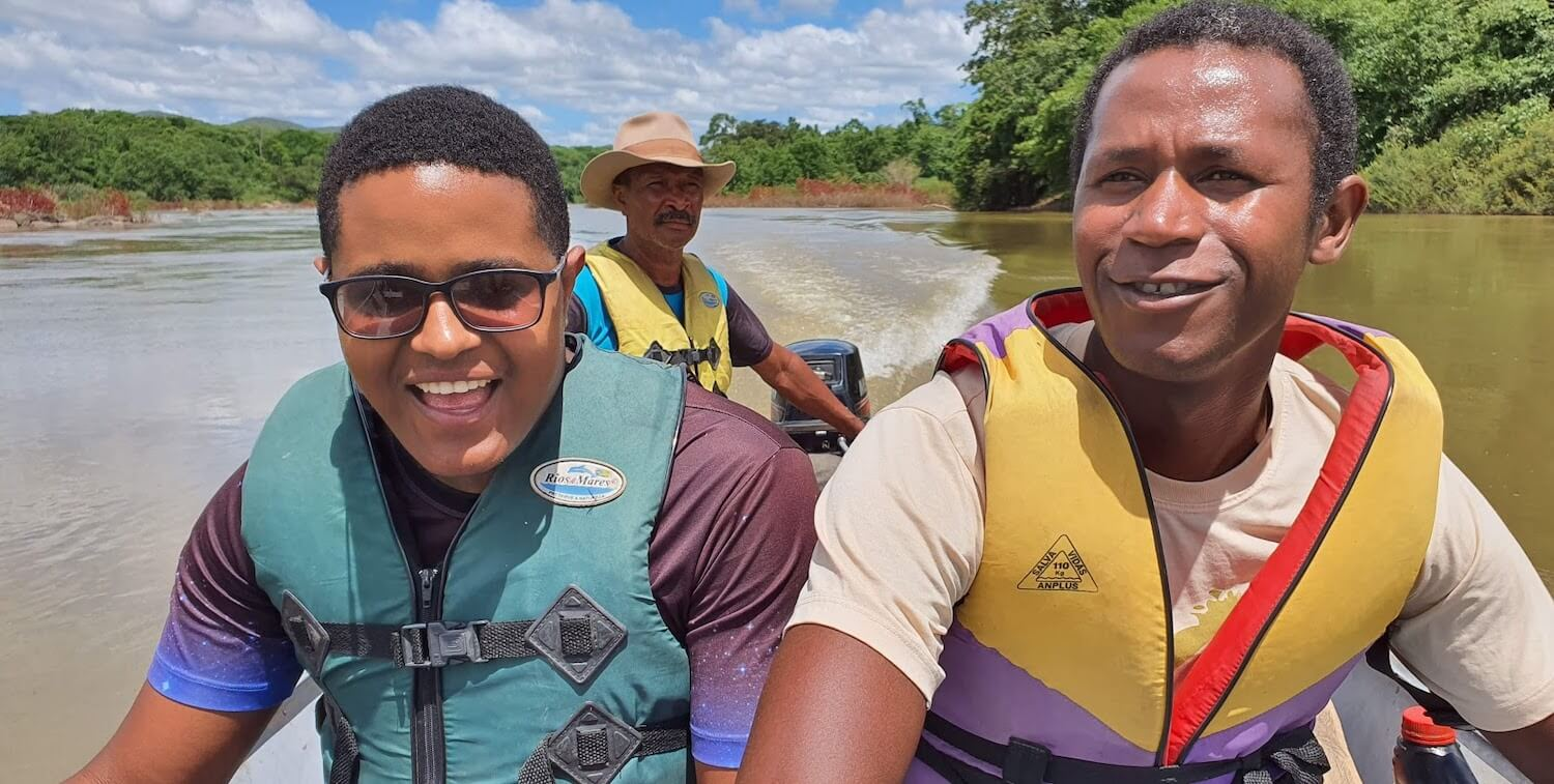 Three men in small motorboat wearing lifejackets and smiling.
