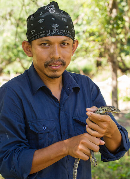 Close-up of Deni Purwandana wearing a black bandana on his head and holding a small Komodo dragon hatchling with both hands.