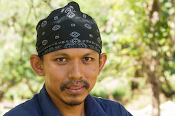 Head shot of Deni Purwandana looking at camera, black bandana covering head.