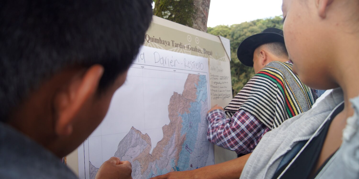 A few people looking at map on poster board.