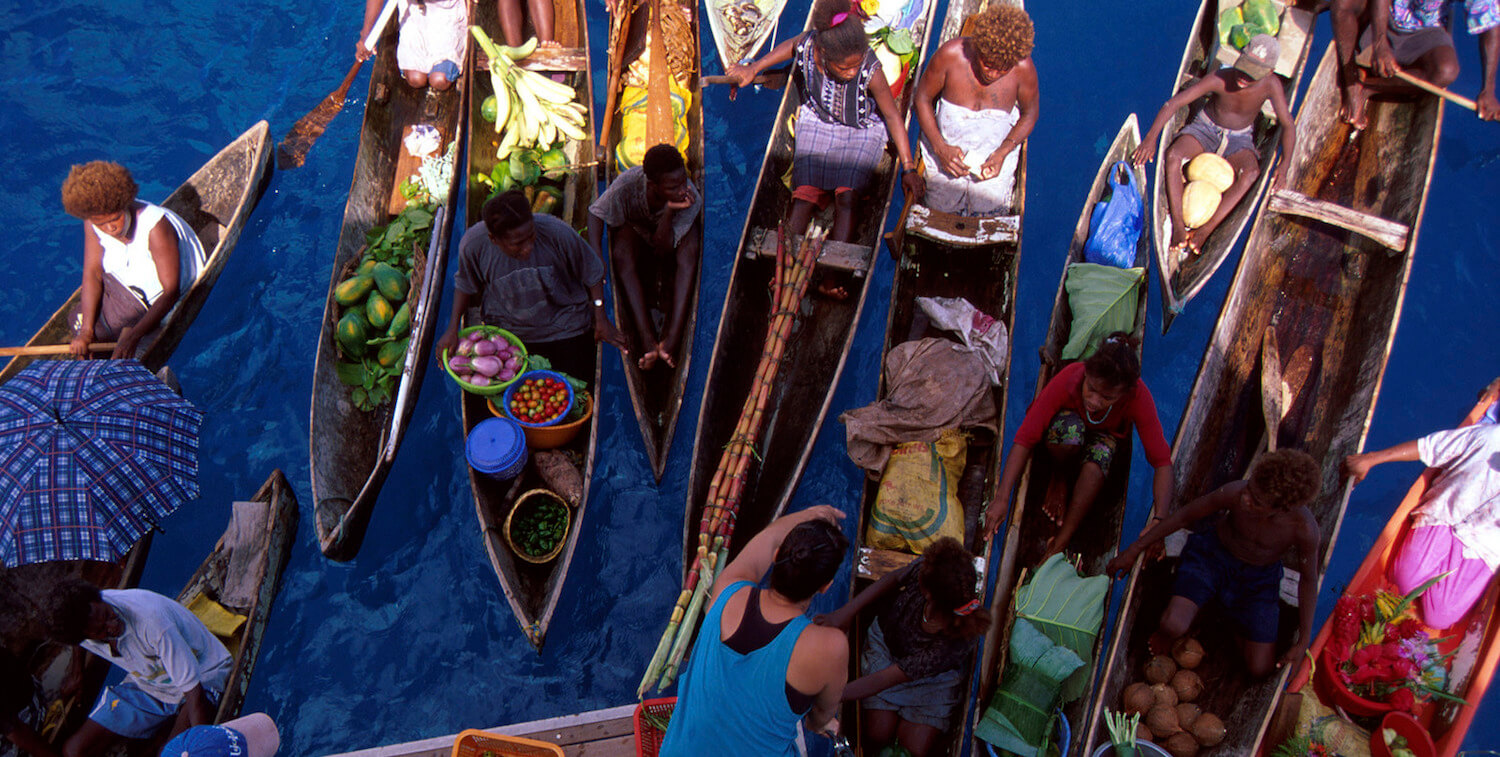 Aeriel view of crowded canoes on water, carrying produce.