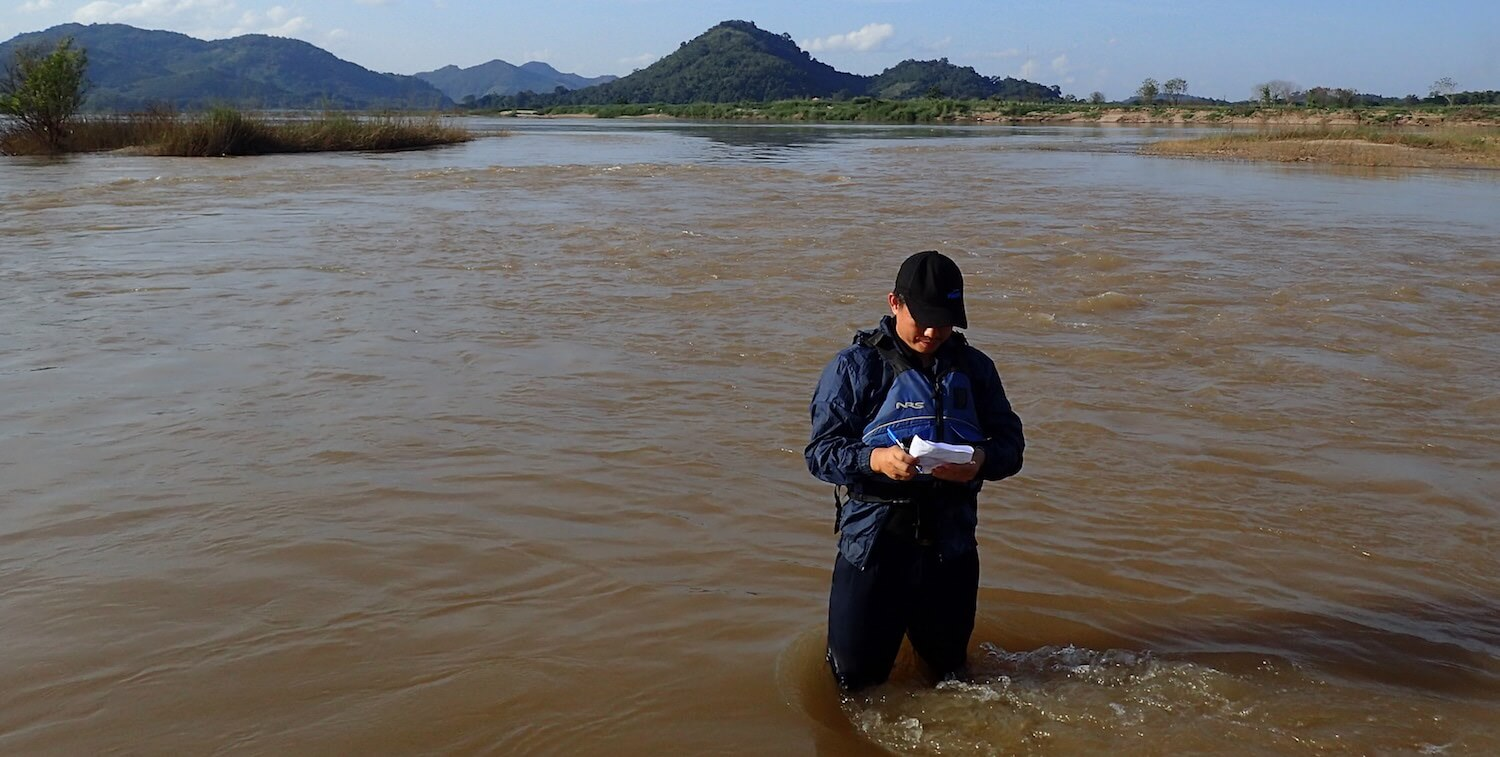 Man standing knee-deep in water, writing in notebook.