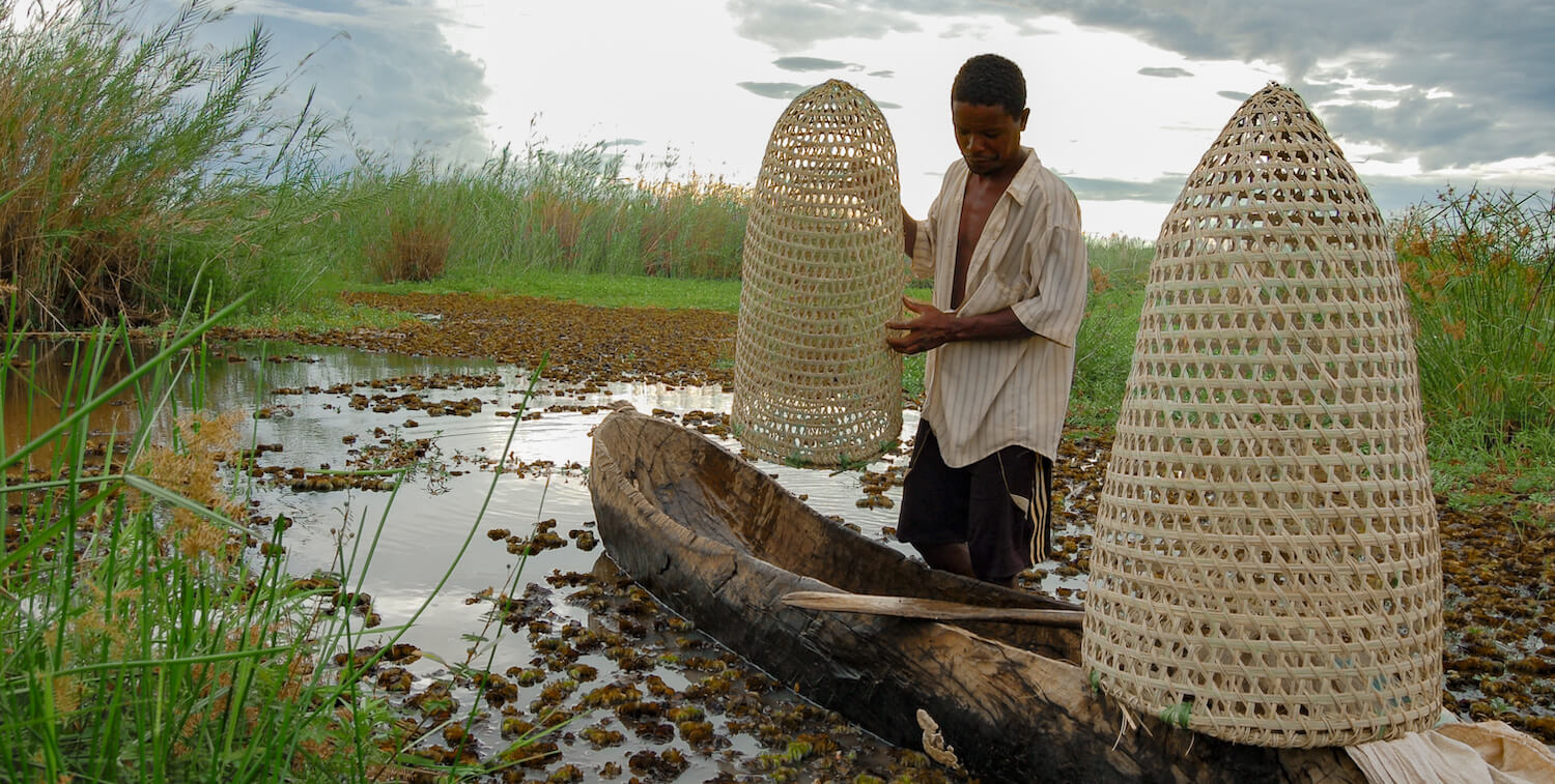 Man standing next to canoe in shallow water that holds two cone-shaped fish traps.