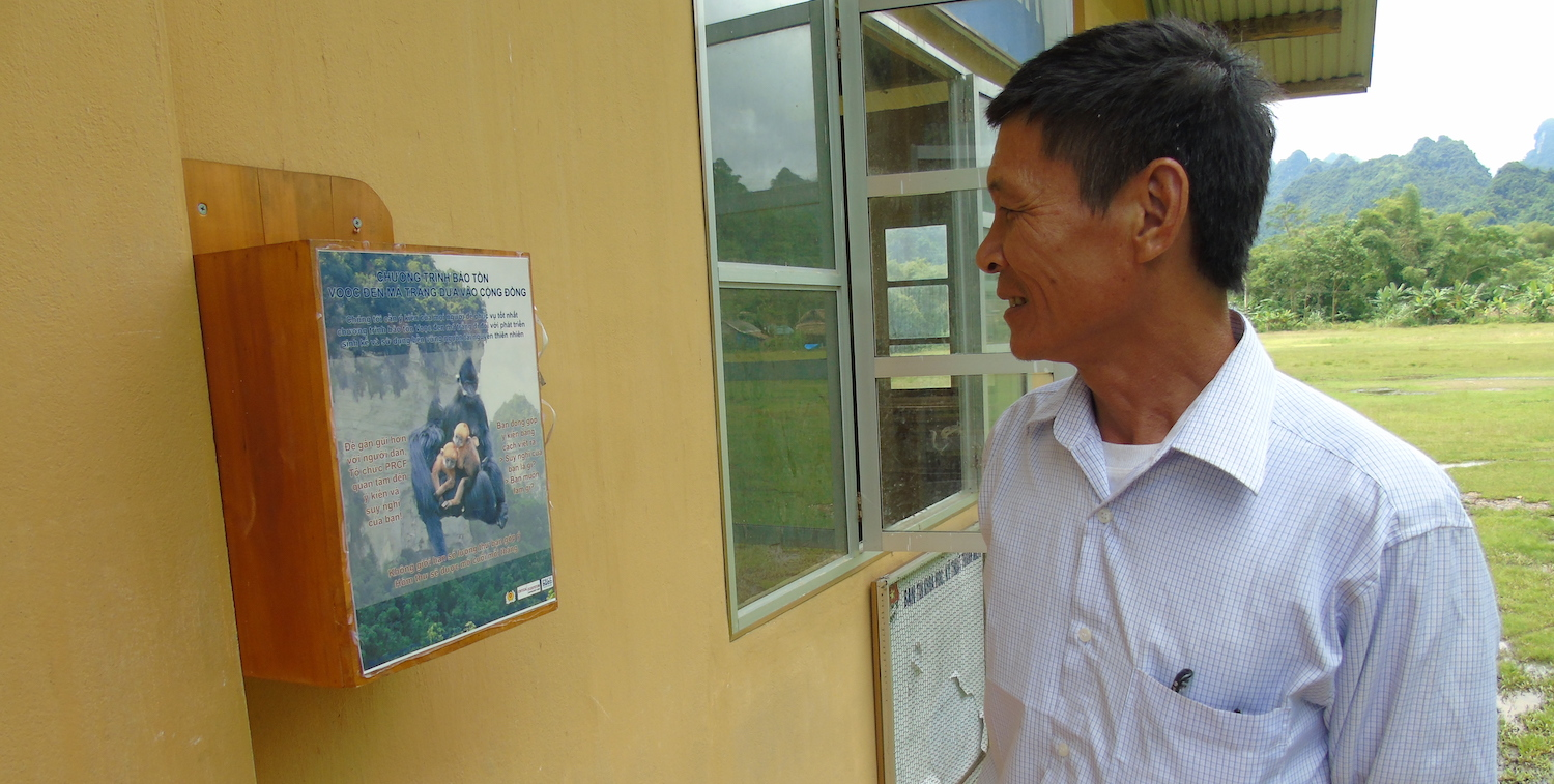 Man looking at poster on outside wall.