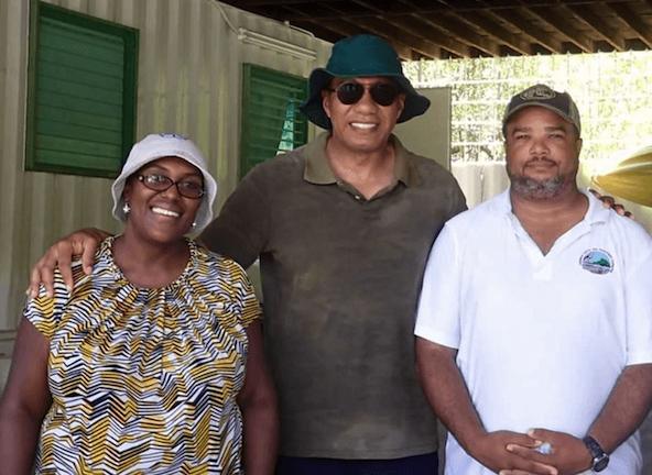 Ingrid standing next to 2 men, all 3 smiling at camera.