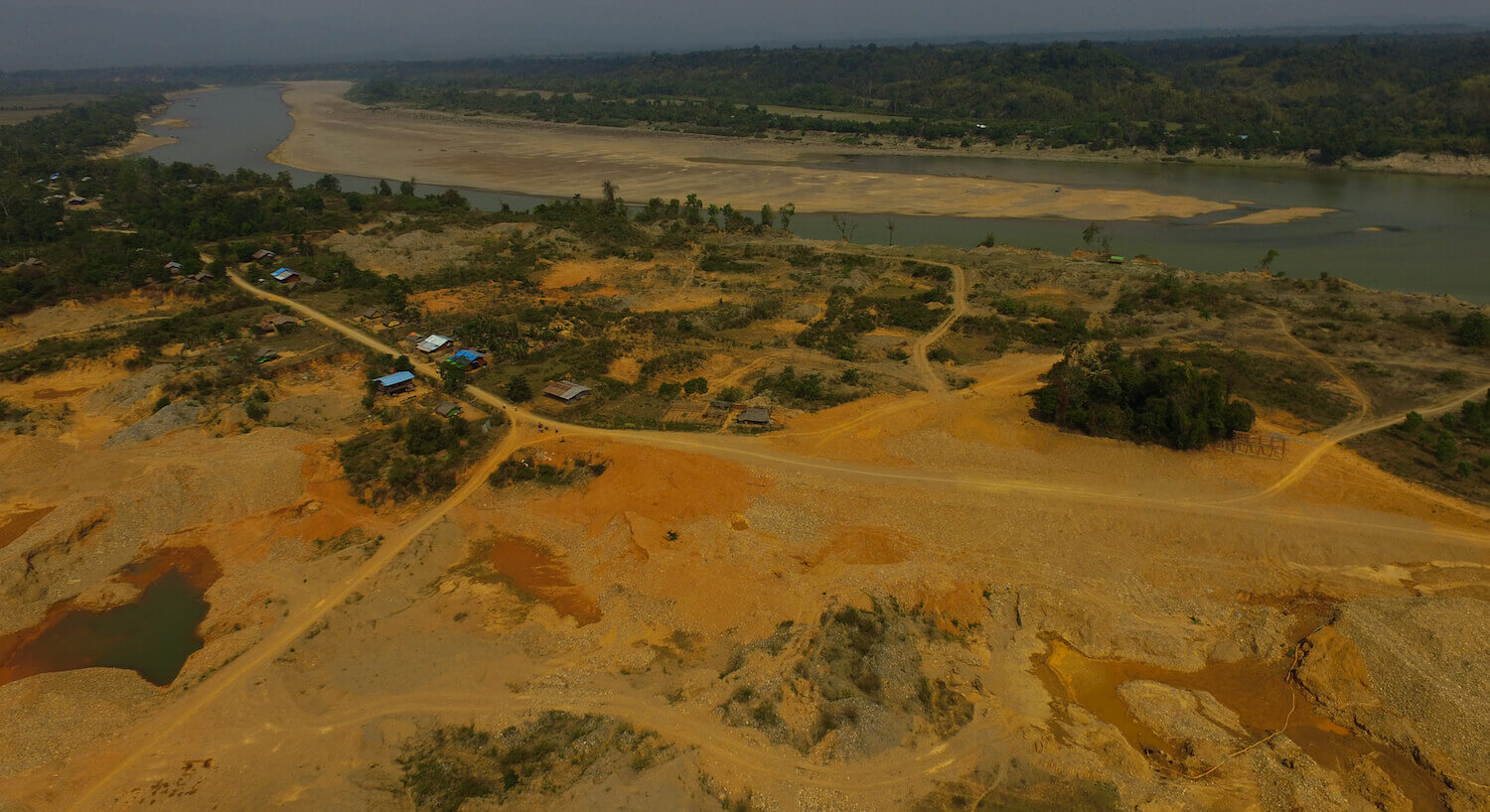 Aerial view of golden, barren landscape with road intersecting. River in background.