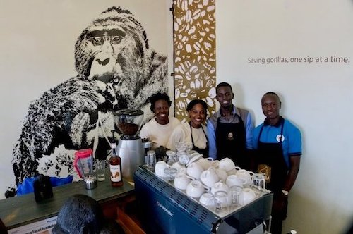 Four people standing behind coffee counter, smiling. Large drawing of gorilla on wall behind them.
