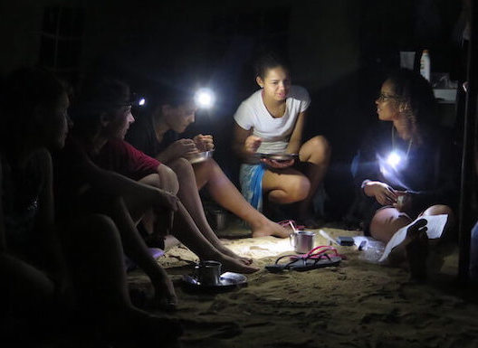 About 5 people with headlamps sit on sand.
