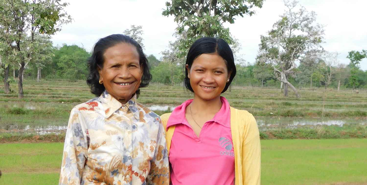 Two smiling women stand in front of green rice paddies and forest.