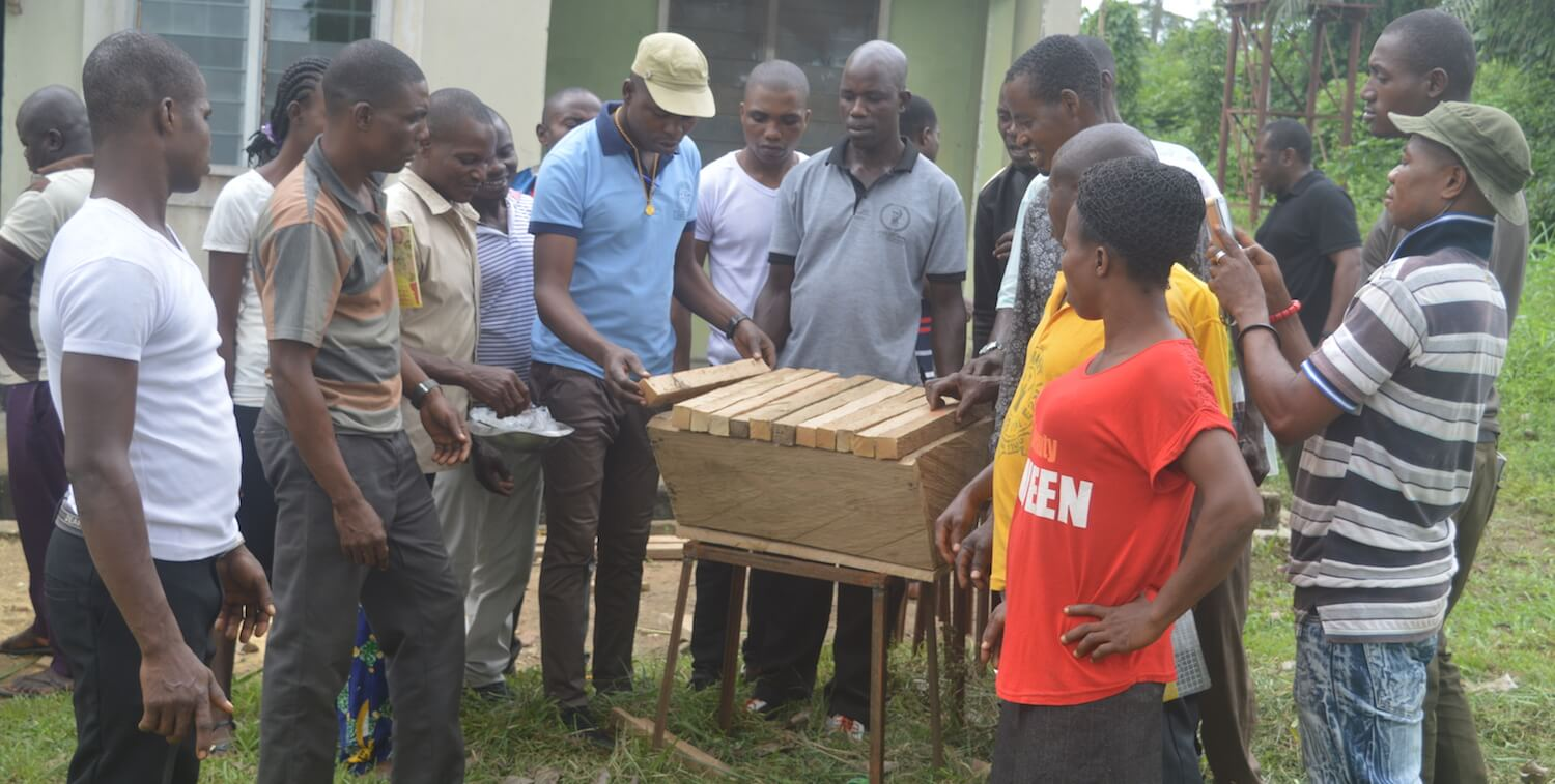 Man finishing wooden beehive while group of people around him observes.