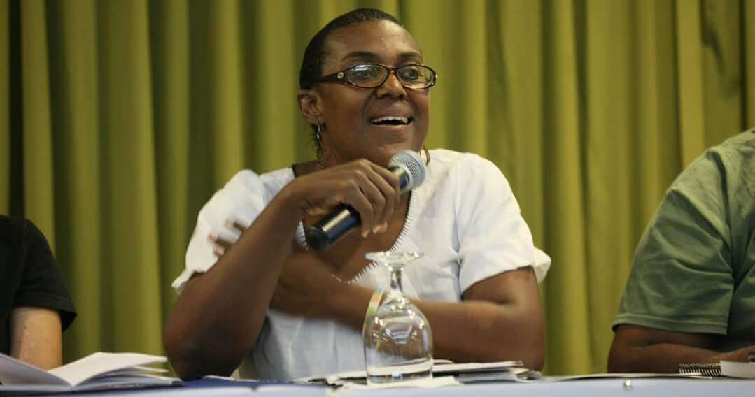 Ingrid sitting at panel table, smiling and speaking into microphone.