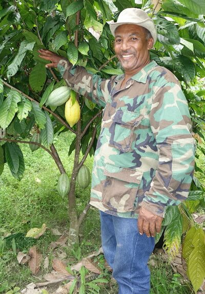 Man standing proudly next to his cocao tree.