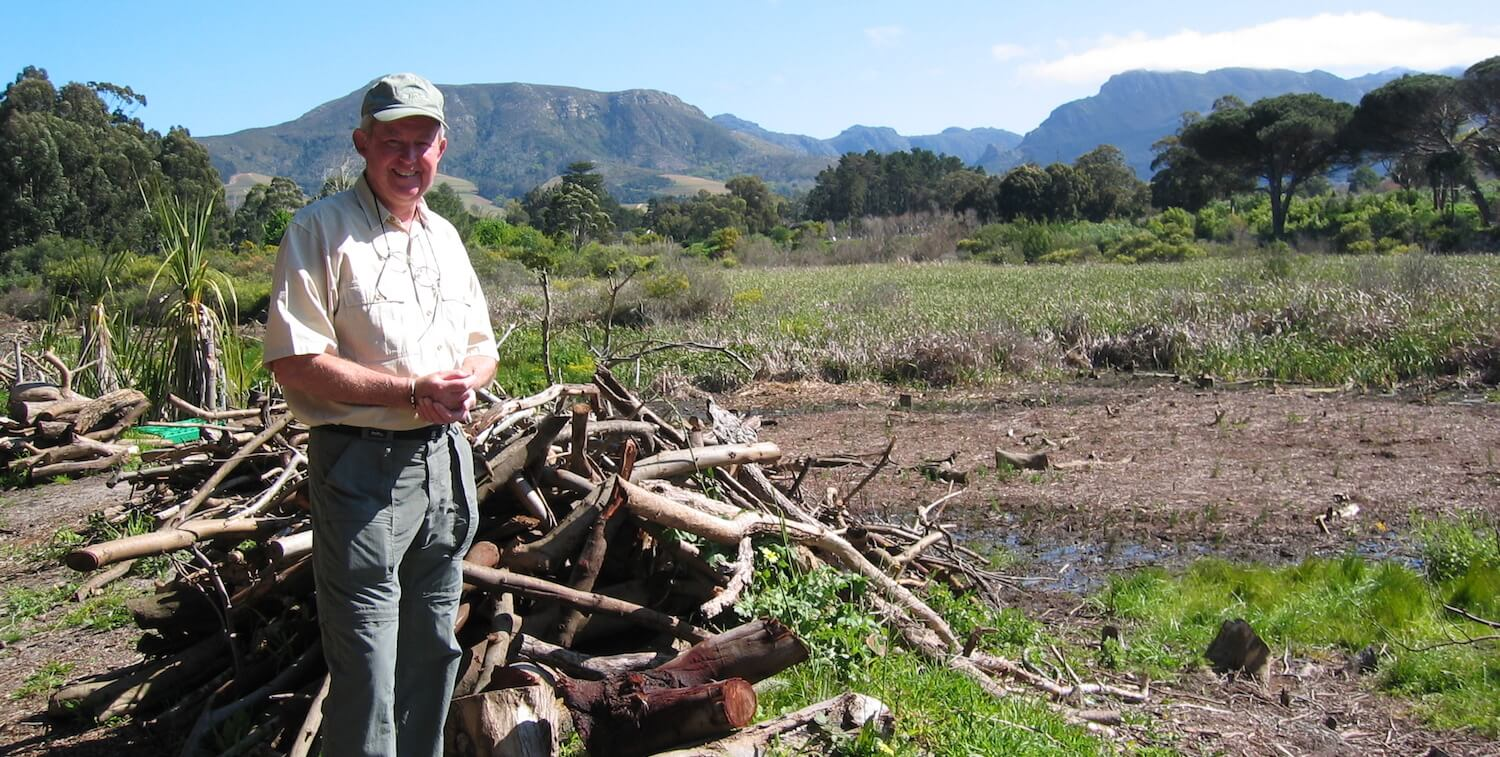 Man standing outside, smiling at camera. Pile of branches behind him, mountain in the background.
