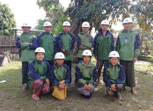 Group of 10 men and women, wearing white hard hats and matching green jackets.