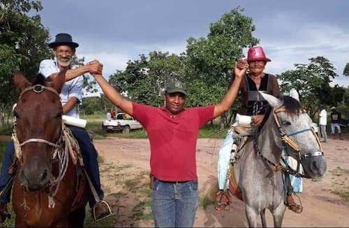 Man holds hands with man and woman on horseback on either side of him.