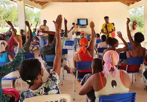 People raise hands during meeting in open-air building.