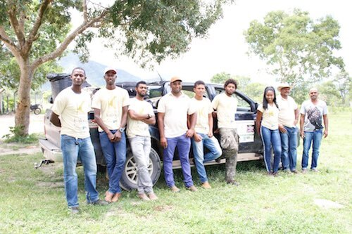 Group of young adults standing in front of pick-up truck.