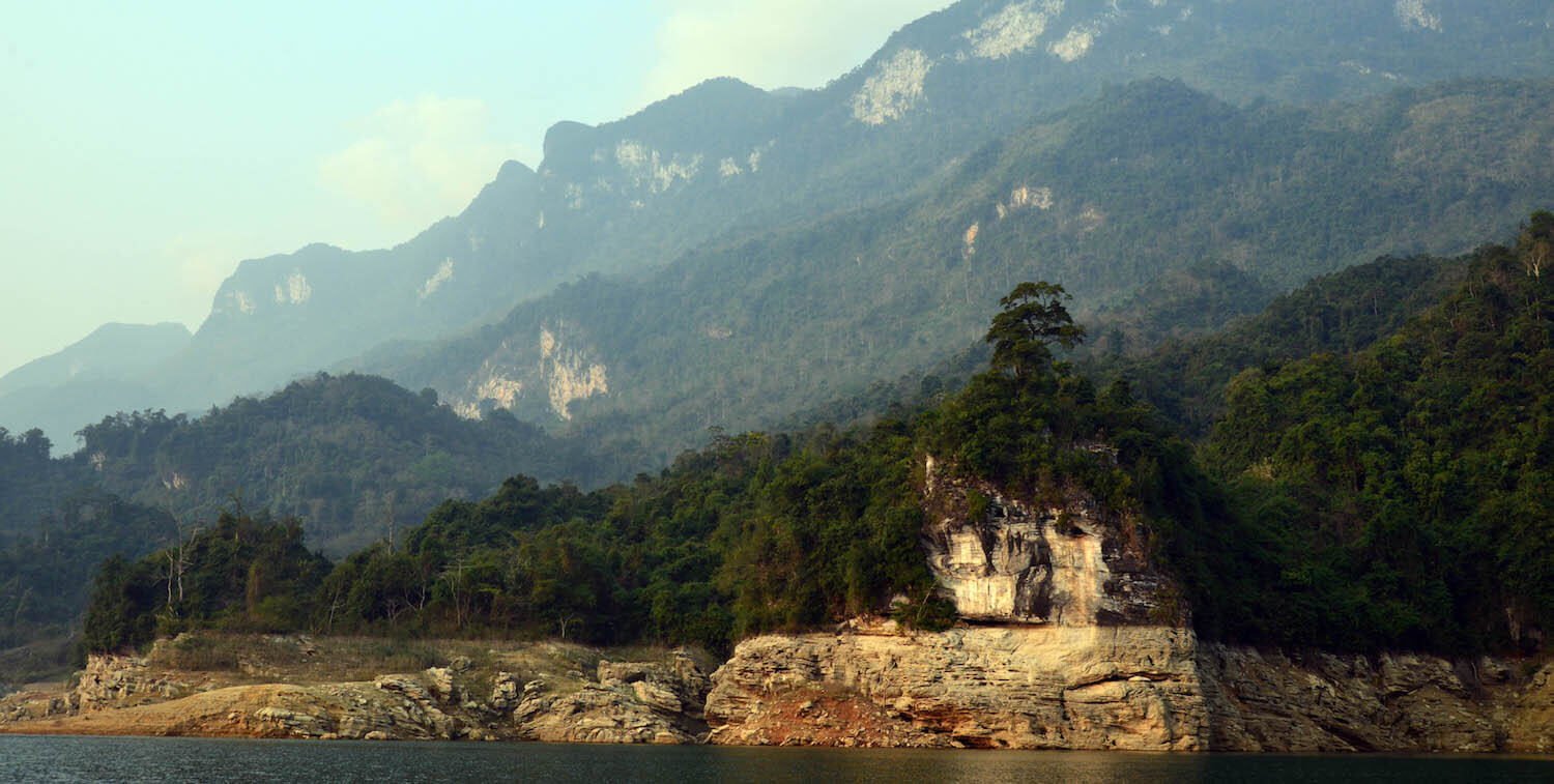 Water in foreground, karst wall and then mountains in background.