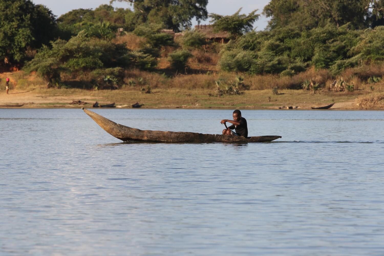 Man paddling wood canoe.