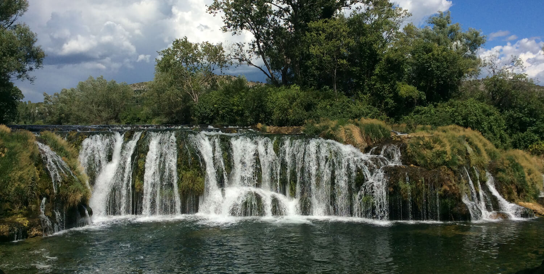 Small, long waterfall amidst greenery.