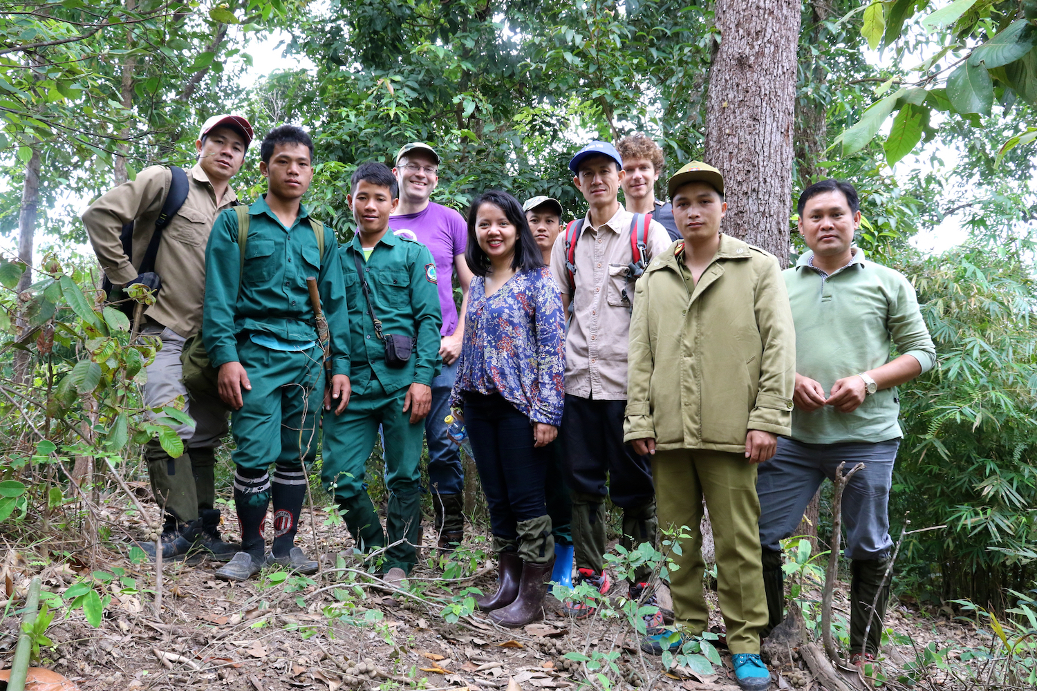 9 men and 1 women in forest, smiling at camera.