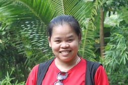 Head shot of Le Thi Trang, outside with plants in background