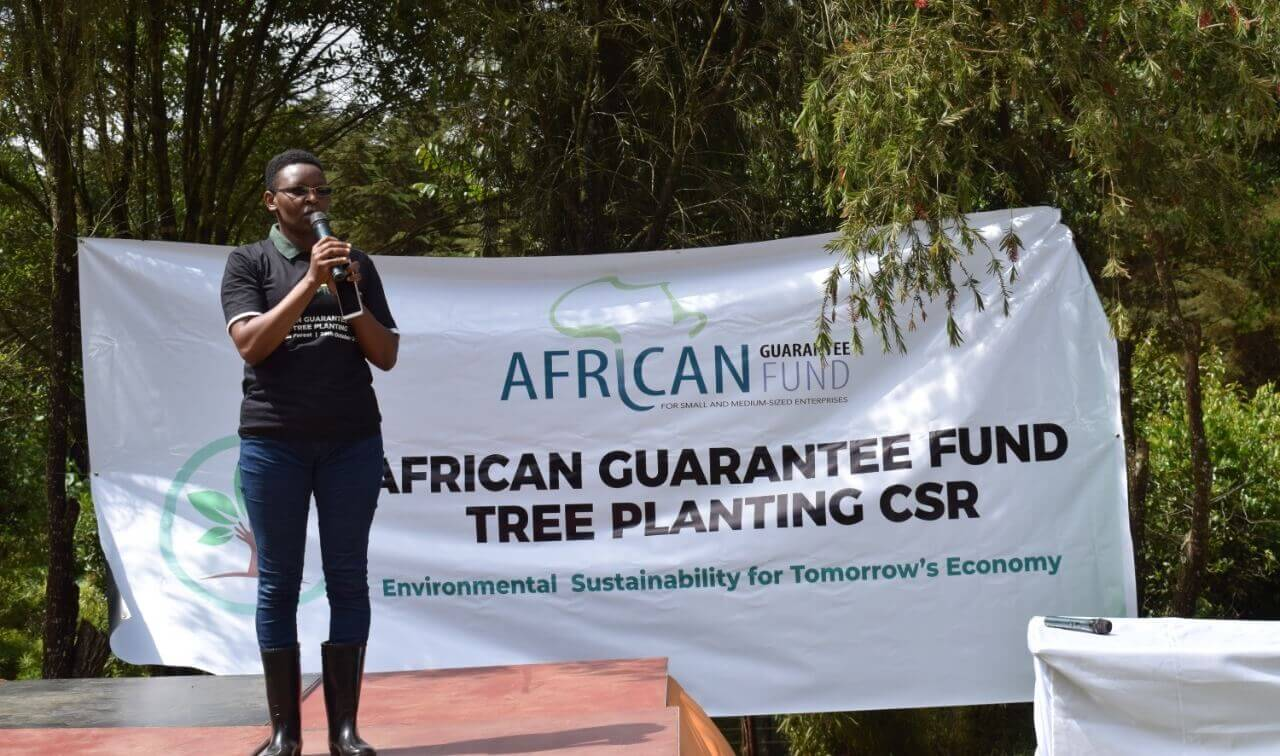 "Leah stands on stage, large banner reading African Gaurantee Fund Tree Planting CSR"" behind her."