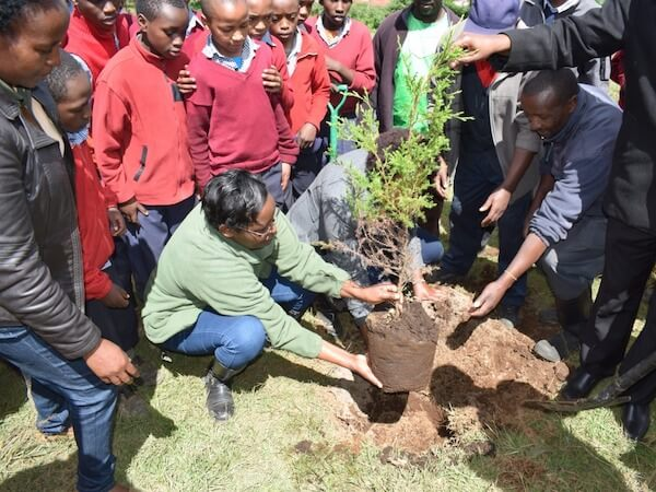 Leah planting a small tree with a few adults and a few schoolchildren in red sweaters standing around her.