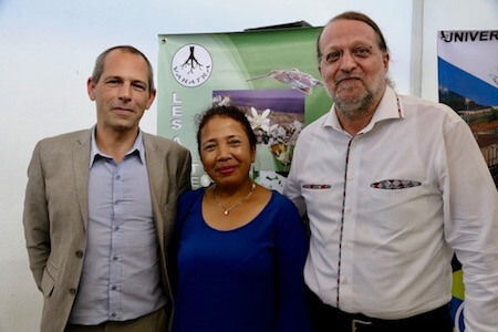 Two men, one woman, standing together, smiling at camera.