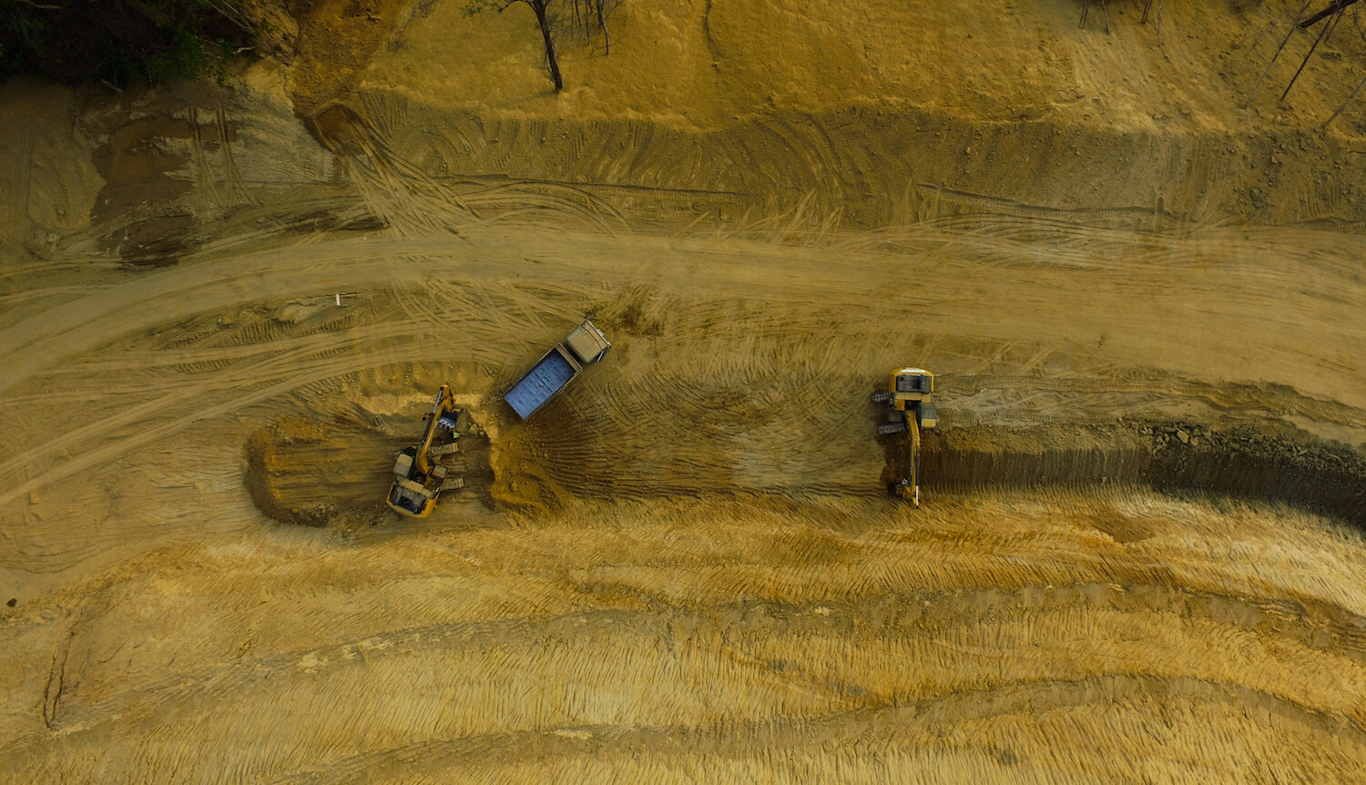 Aerial view, 2 trucks in the middle of barren, gold landscape.